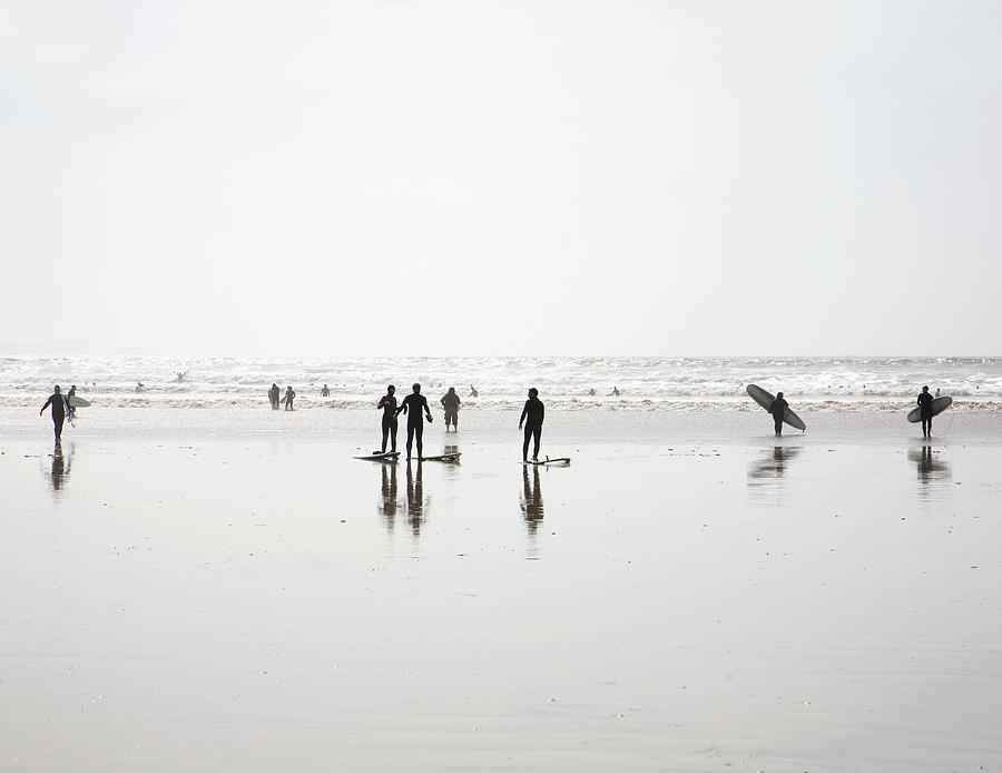 Group Of Surfers Walking On Beach Photograph by Ashley Jouhar