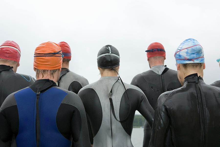 Group Of Triathletes Standing By Lake Photograph by Lothar Schulz