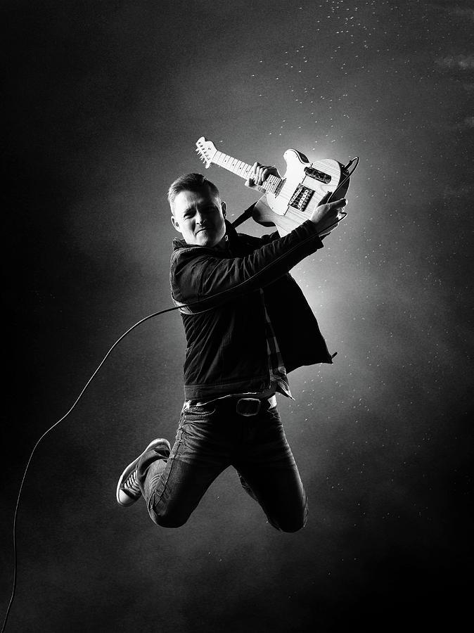Guitarist Jumping High Photograph