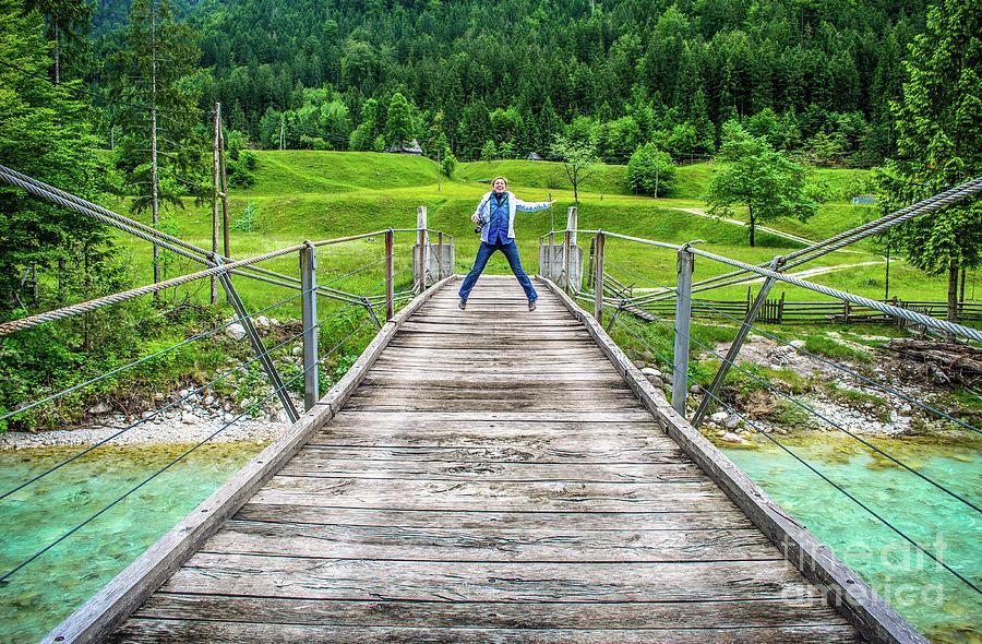 happy distant woman jump of a wooden pedestrian bridge footbridge over river Soca in Slovenia in  wild nature background by Luca Lorenzelli