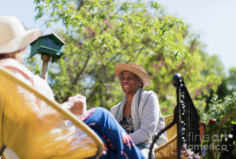 Active Seniors Photograph - Happy Senior Women Friends Talking On Sunny Patio by Caia Image/science Photo Library