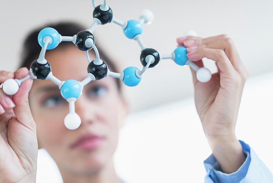 Hispanic Scientist Examining Molecular Photograph by Jgi/tom Grill