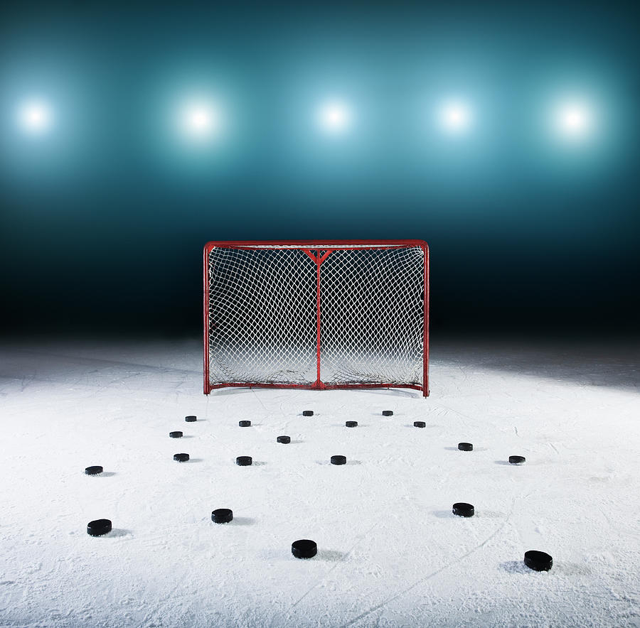Ice Hockey Goal Surrounded By Pucks Photograph by Robert Decelis Ltd