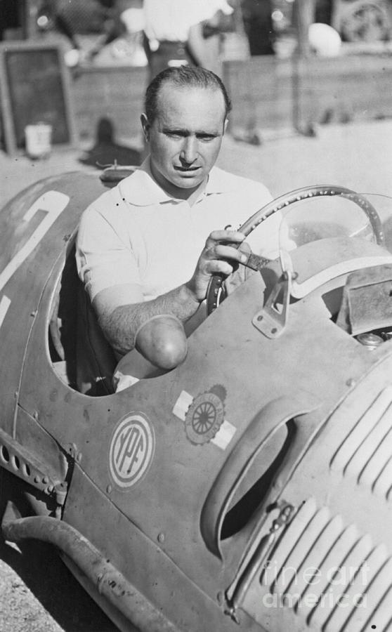 Juan Manuel Fangio Sitting In Race Car Photograph by Bettmann