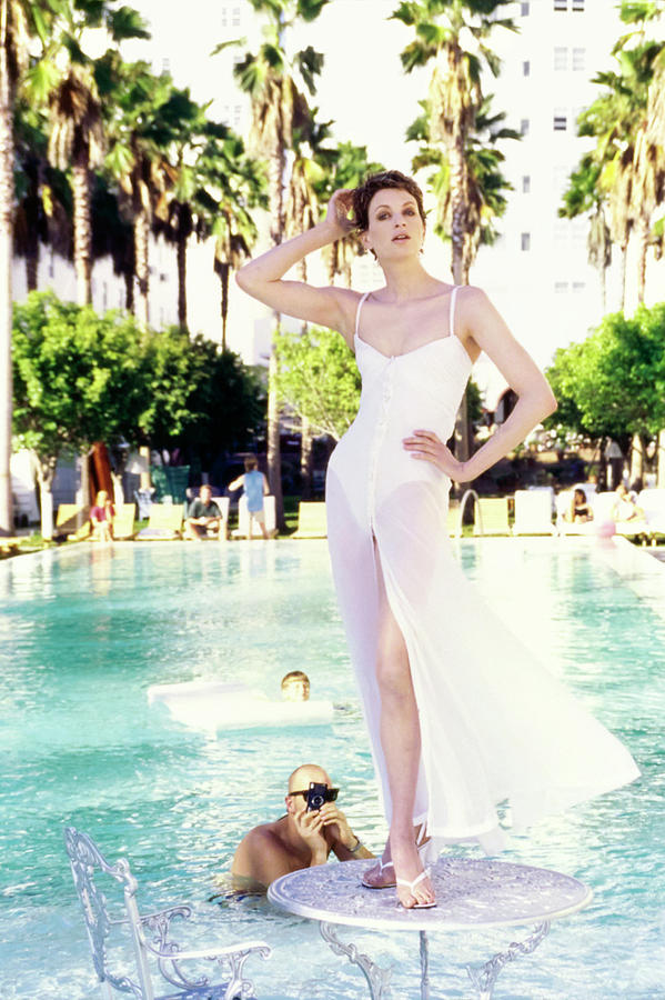Kristen Mcmenamy Wearing A White Dress By A Pool Photograph by Arthur Elgort