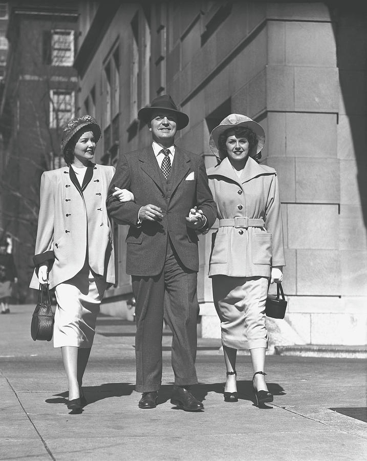 Man And Two Women Walking On Sidewalk Photograph by George Marks
