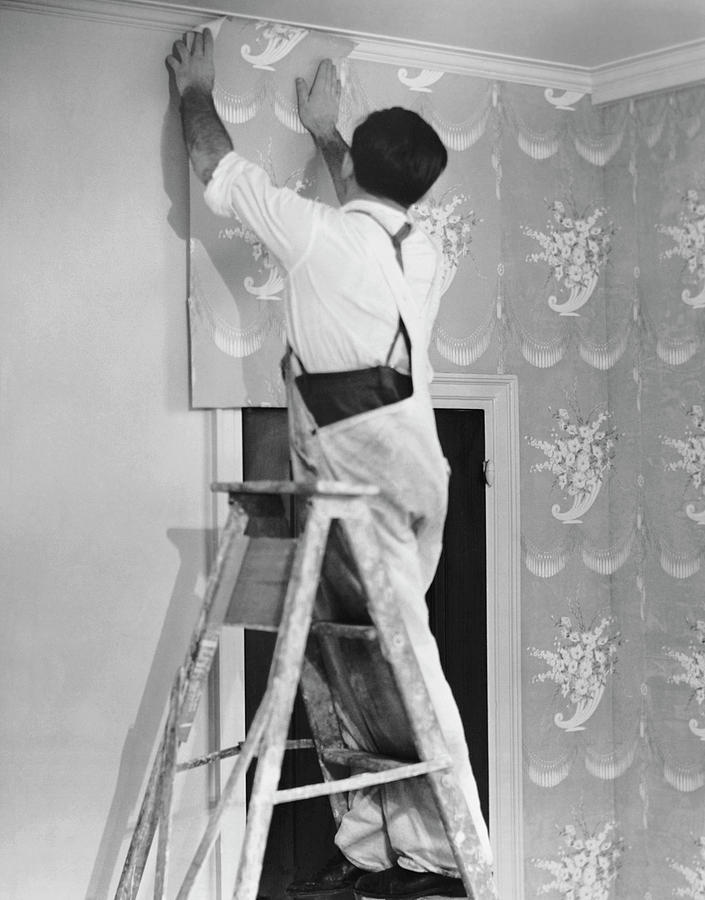 Man Applying Wallpaper Photograph by George Marks