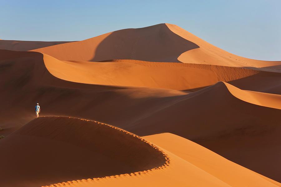 Man Climbing Sand Dunes, Namib Desert Photograph by Peter Adams