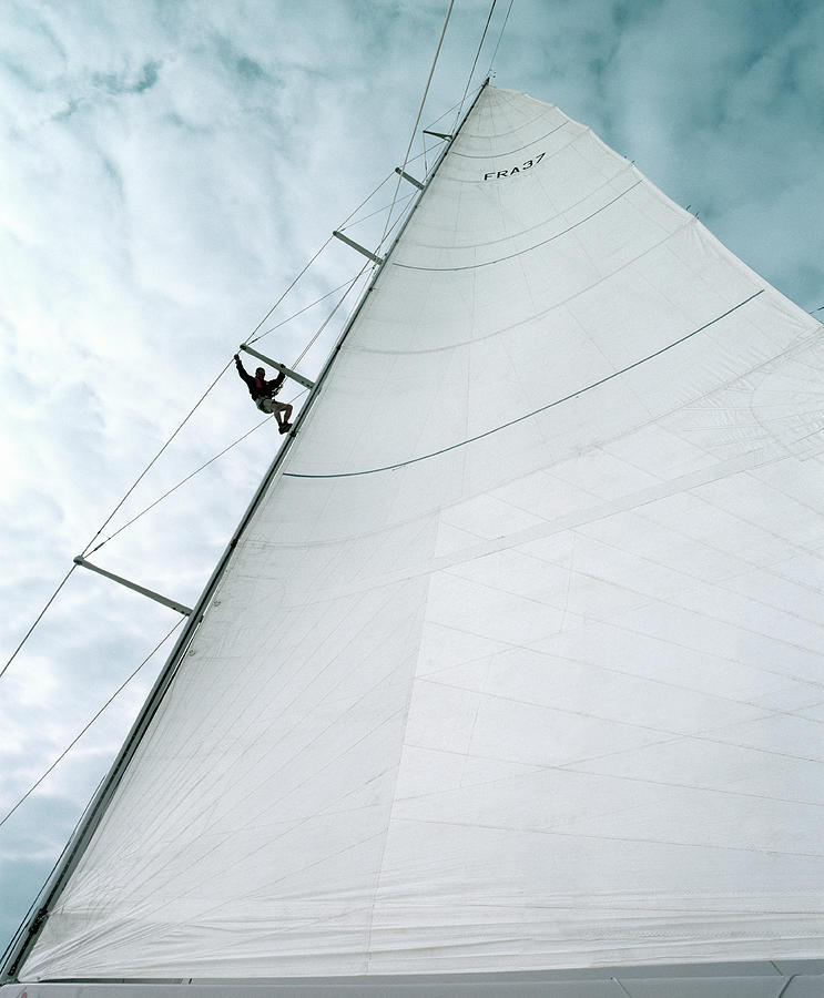 Man Descending Side Of Yachts Sail Photograph by Alan Thornton