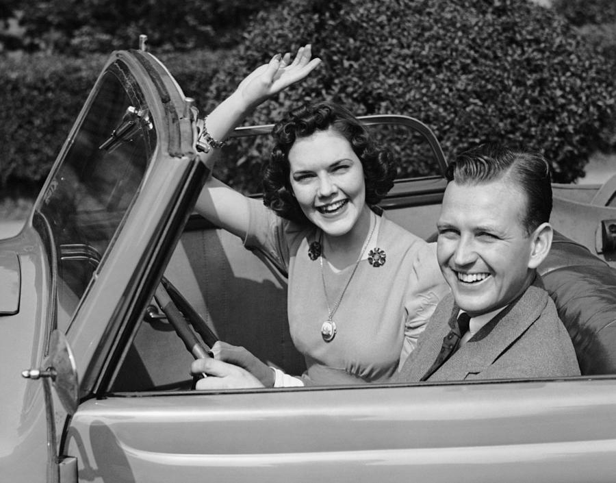 Man Driving Car And Woman Waving Photograph by George Marks