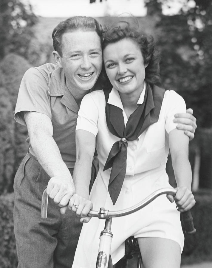 Man Embracing Woman Sitting On Bike Photograph by George Marks
