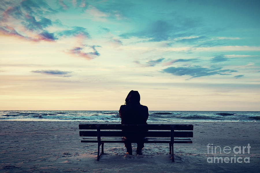 Sea Photograph - Man In Hood Sitting On A Lonely Bench On The Beach by Michal Bednarek