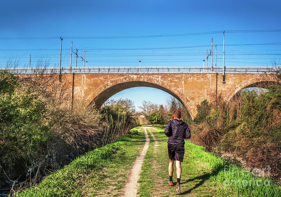man jogging urban park bridge railway path trail in the city background by Luca Lorenzelli