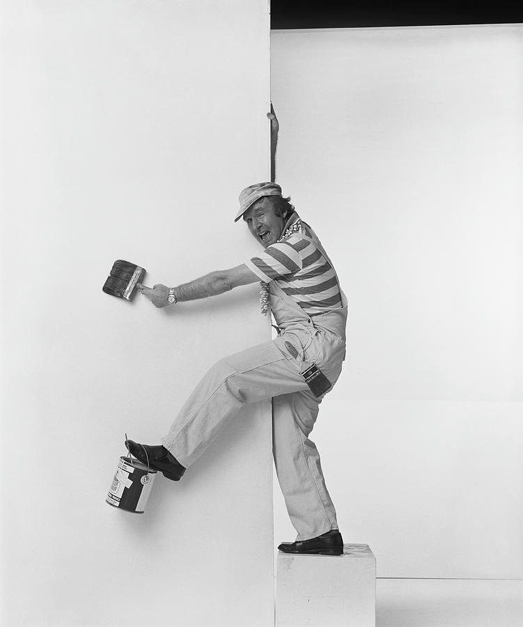 Man Leaning On Wall Holding Paint Photograph by Tom Kelley Archive