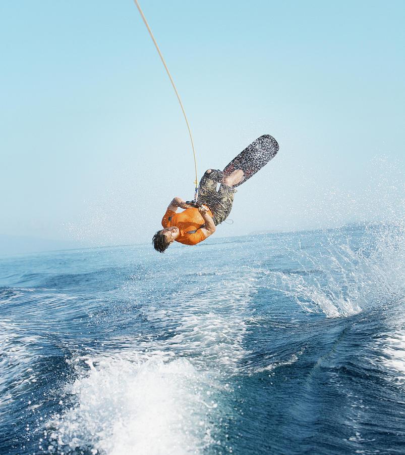 Man Performing Wakeboarding Stunt At Sea Photograph by Paul Bradbury