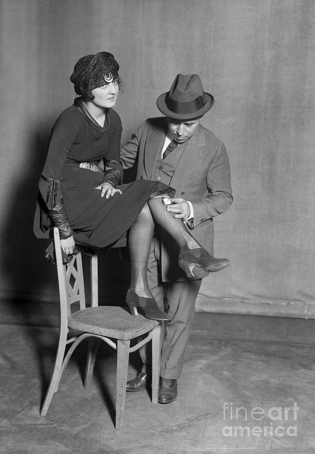 Man Placing Pedometer On Females Leg Photograph by Bettmann