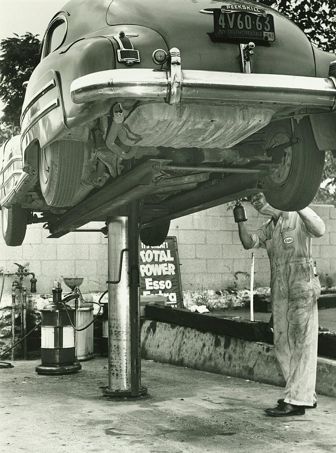 Man Repairing Uplifted Car, B&w, Low Photograph by George Marks