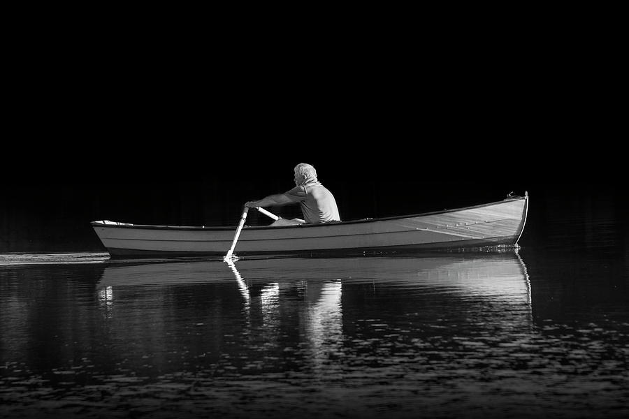 Man rowing on Stoney Lake at Sunrise in Black and White by Randall Nyhof
