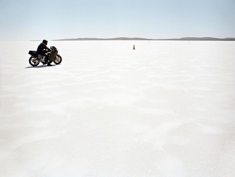 Man Sitting On Motorcycle On Salt Flat Photograph by Tobias Titz