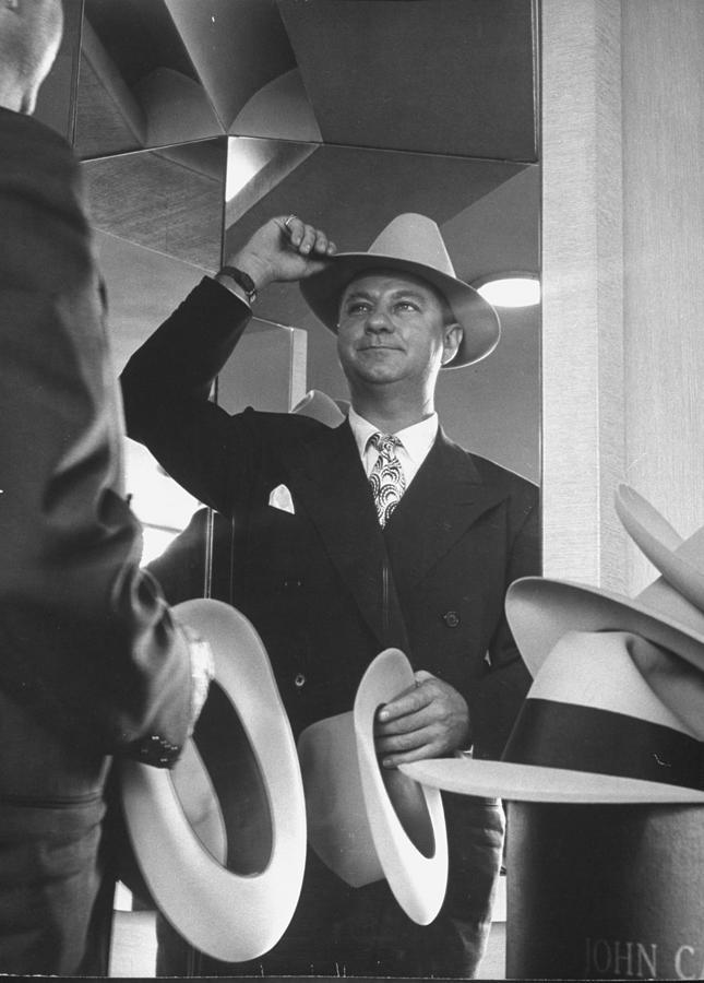 Man Trying On Hats At Nieman Marcus Depa Photograph by Nina Leen