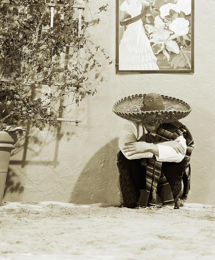 Man Wearing Hat, Crouching By Wall Photograph by Lisa Peardon