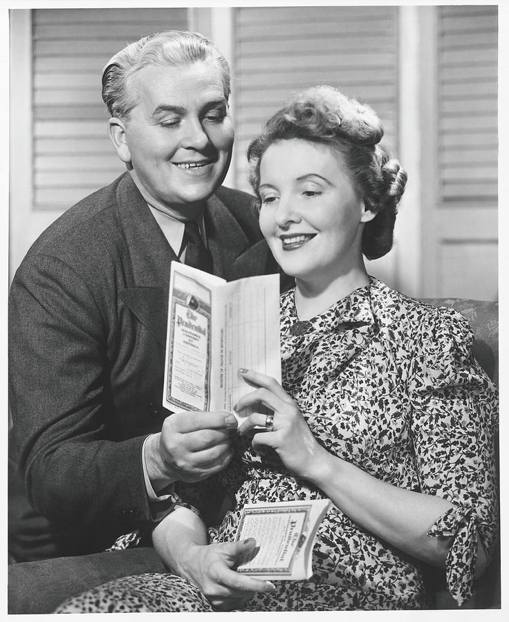 Mature Couple Looking At Brochure, B&w Photograph by George Marks