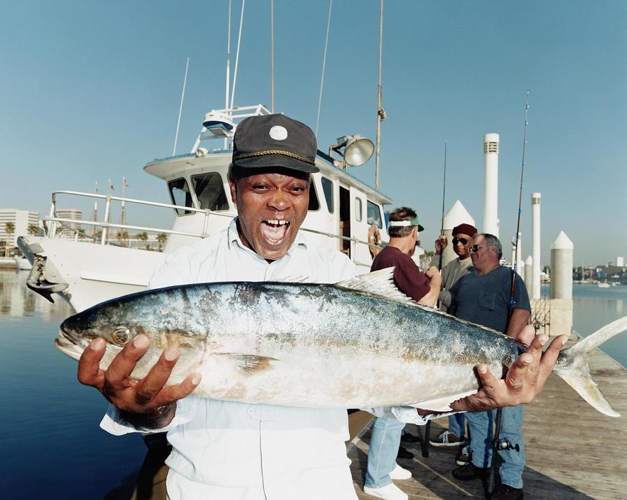 Mature Man Holding Yellowtail Fish On Photograph by Sean Murphy