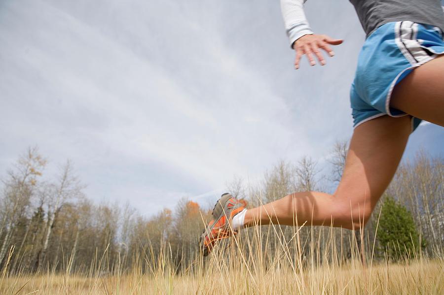 Mature Woman Running Through Tall Photograph by Caroline Woodham