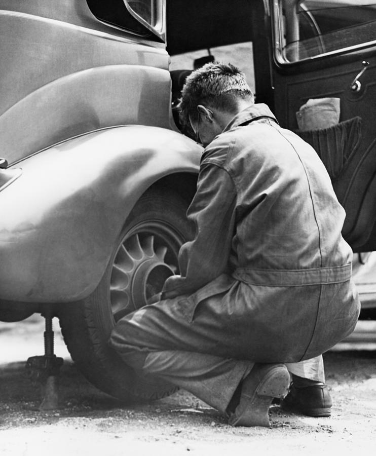 Mechanic Changing Tire On Car Photograph by George Marks