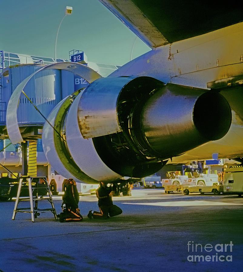 Mechanics working on 767 engine  by Tom Jelen
