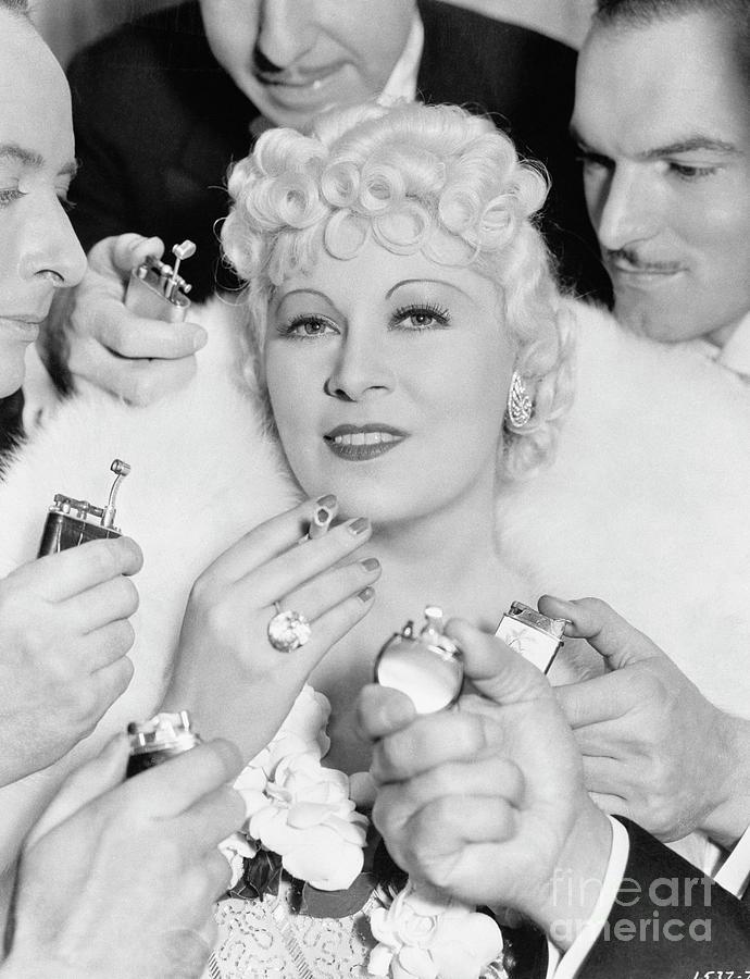 Men Offering To Light Cigarette For Mae Photograph by Bettmann