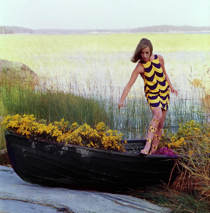 Model In Rowboat Filled With Yellow Flowers Photograph by Gordon Parks