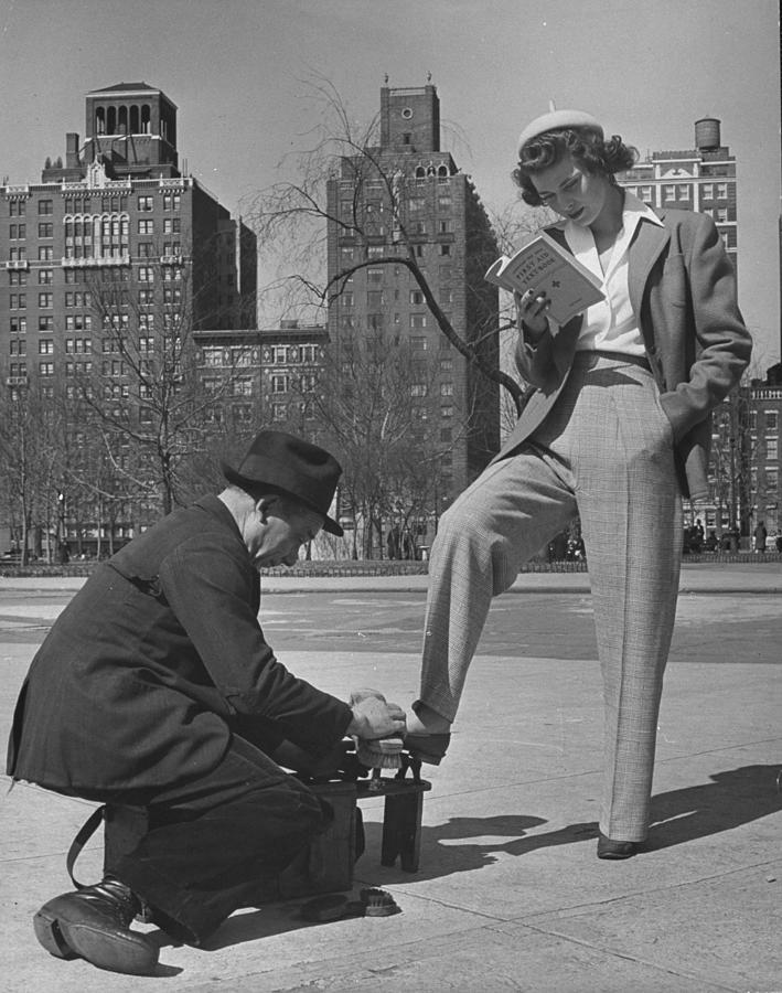 Model Showing Off Slacks As She Reads A Photograph by Nina Leen