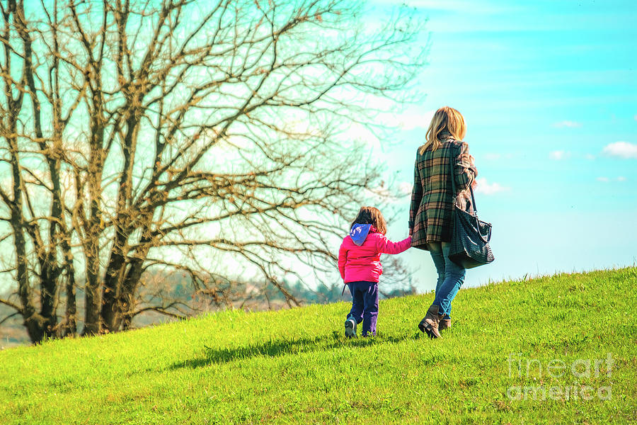 mom and daughter walk together outside by Luca Lorenzelli