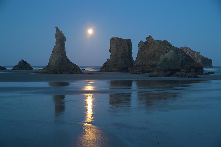 Moon Setting Over Seastacks At Low Photograph by Darrell Gulin