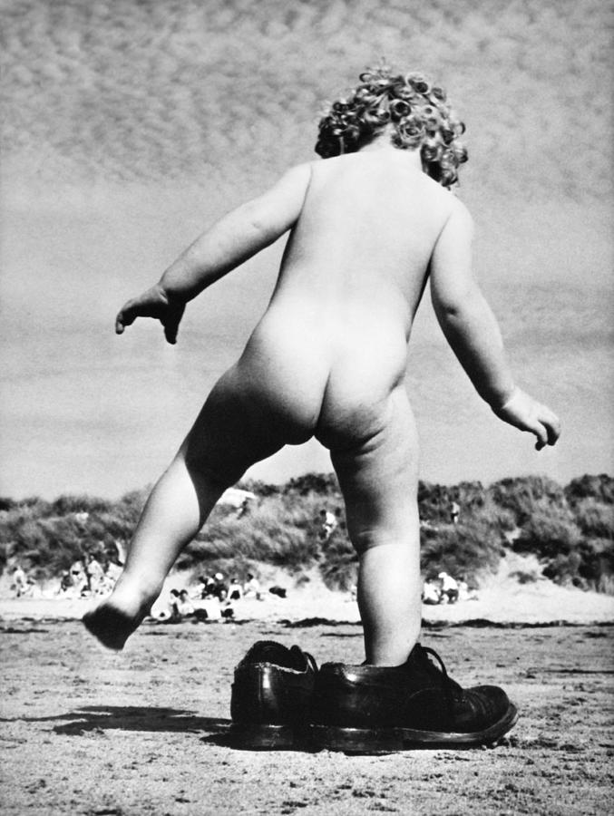 Naked Child On A Beach Trying On Shoes Photograph by Keystone-france