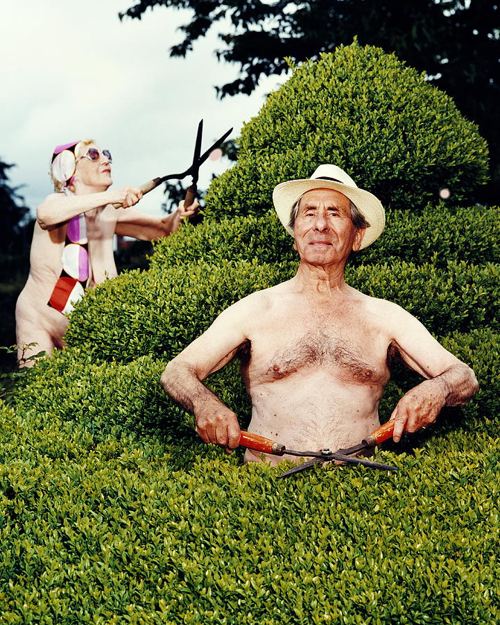 Naked Mature Couple Trimming Hedge, Man Photograph by Chris Craymer