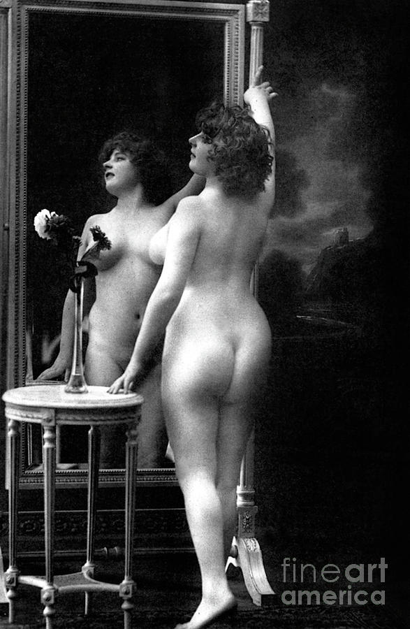 Naked woman posing in front of a mirror near a pedestal table, 1913 by French School