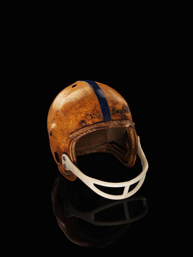 Old Football Helmet On Black Background Photograph by Alexander Nicholson