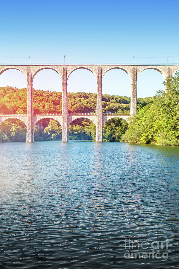 Old stone viaduct over large river between two hills vertical by Gregory DUBUS