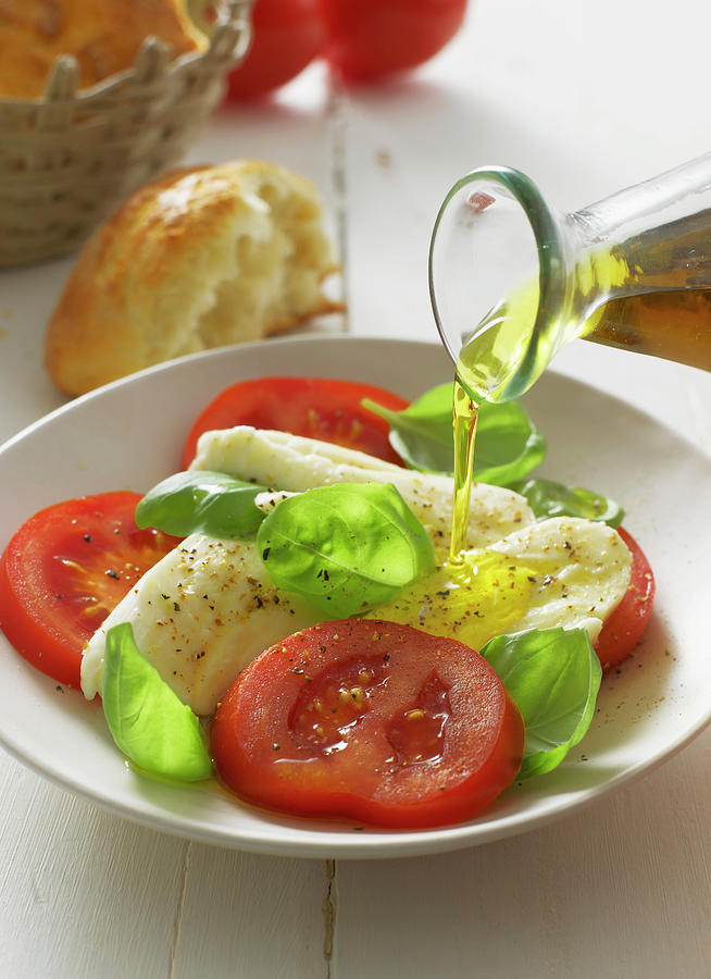 Olive Oil Pouring On Caprese Salad In Photograph by Westend61