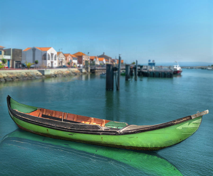On the calm water of the bay sits a green gondola. by Manny DaCunha