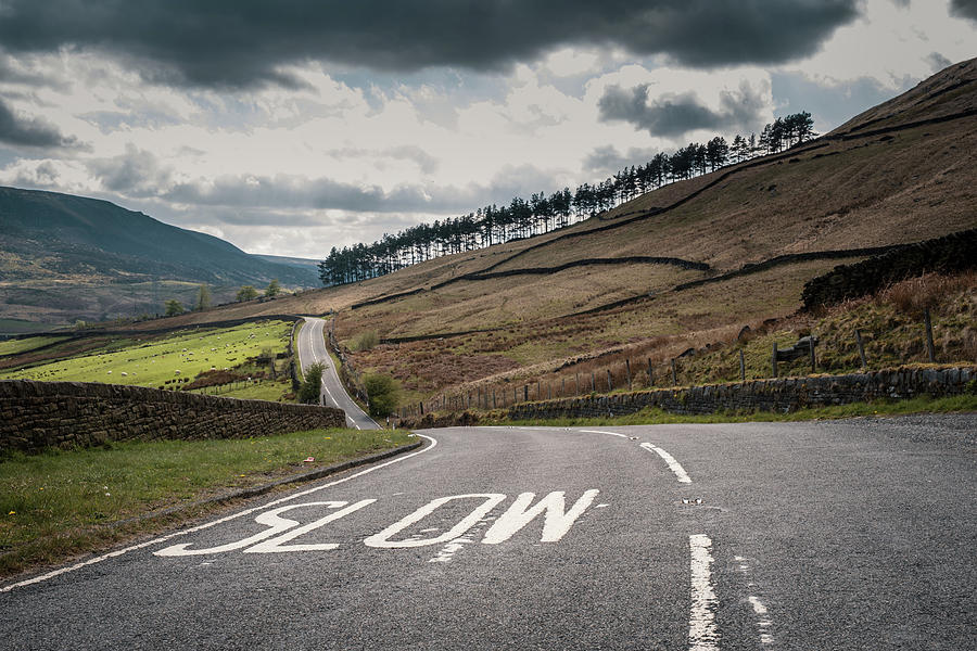 Painted Slow warning sign on winding country road in England Photograph by Jon Ingall
