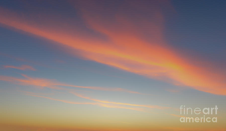 Painterly sunrise sky depicting a diagonal cloud streak in yellow, orange and pink pastel colors by Ulrich Wende
