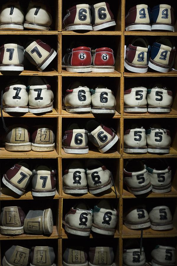 Pairs Of Bowling Shoes On A Shelf Photograph by Rubberball/mike Kemp