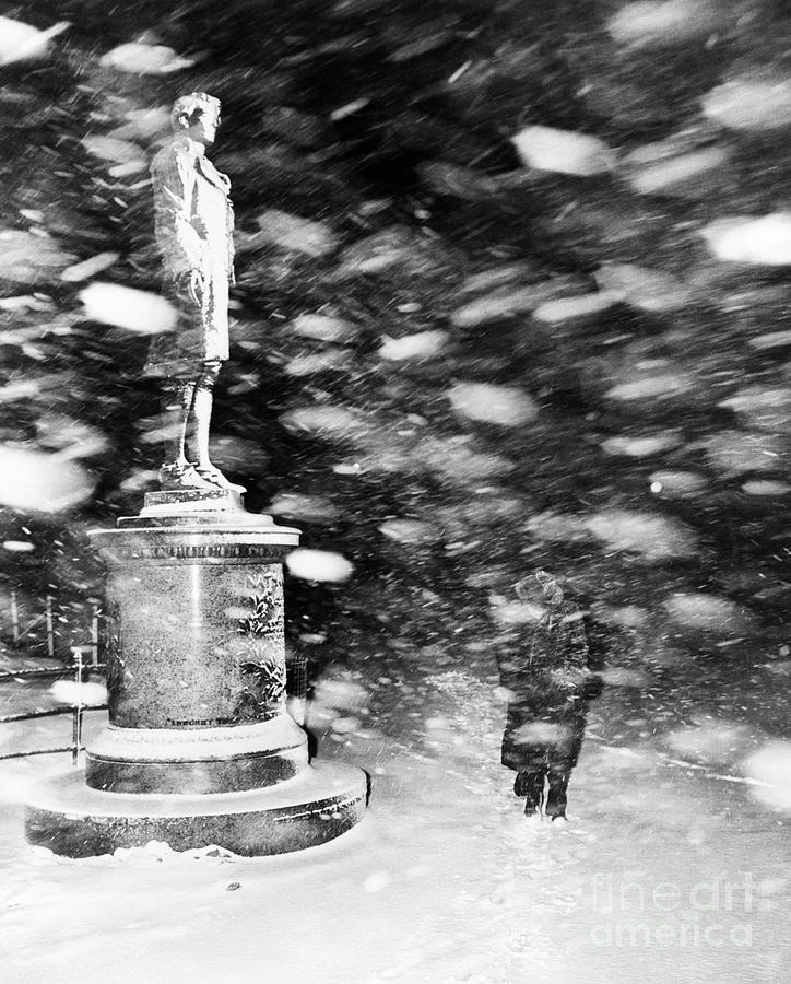 Pedestrian Passing Statue In Snow Storm Photograph by Bettmann