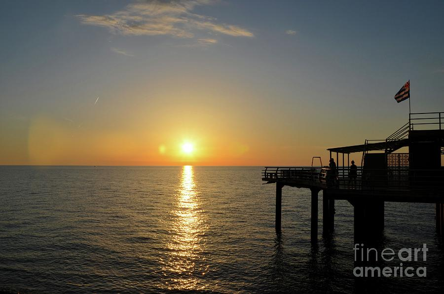 People enjoy sunset over Black Sea horizon at pier with flag Batumi Georgia by Imran Ahmed