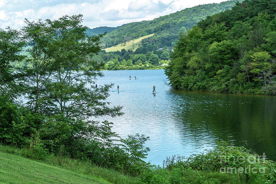 People use stand-up paddleboards on Lake Habeeb at Rocky Gap Sta by William Kuta