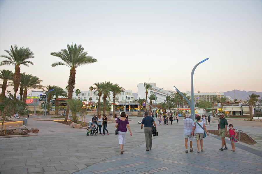 People Walking On Stone Plaza Near Palm Photograph by Barry Winiker