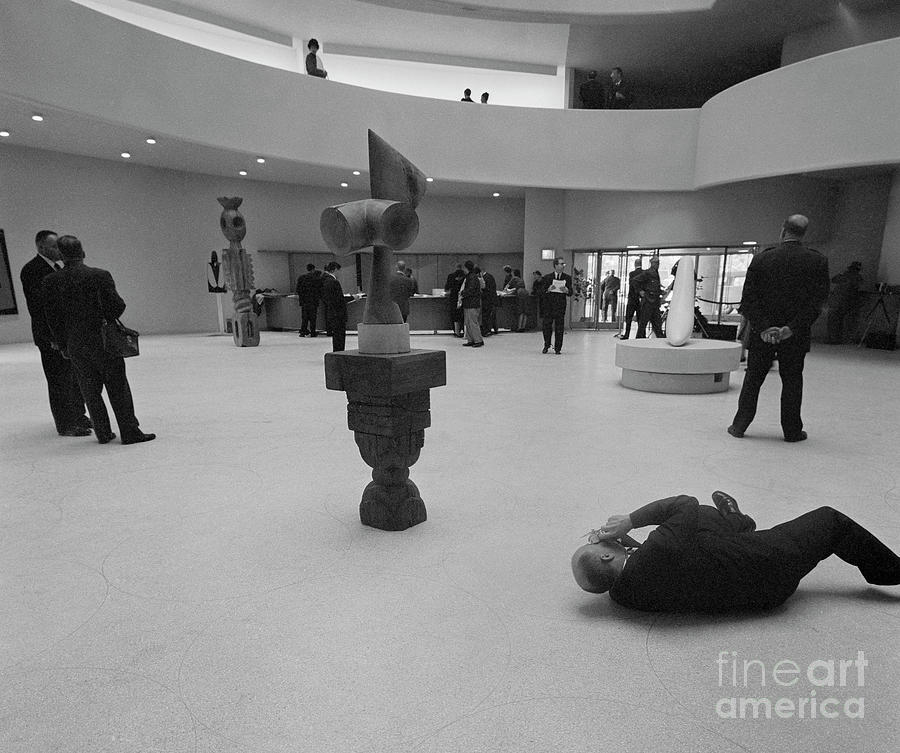 Photographer Lying On Floor And Taking Photograph by Bettmann